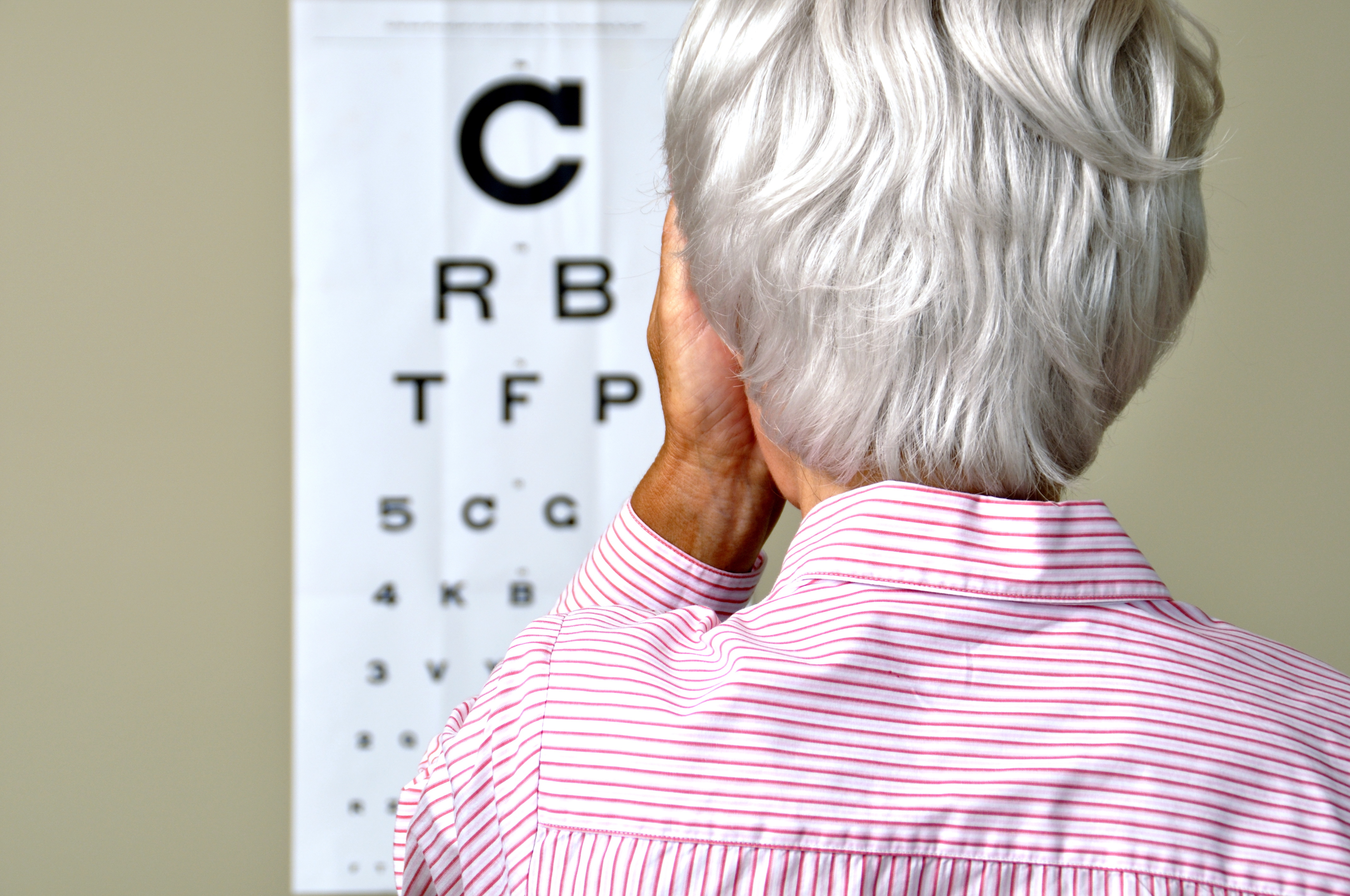 Older woman covering one eye and looking at letters on vision test chart